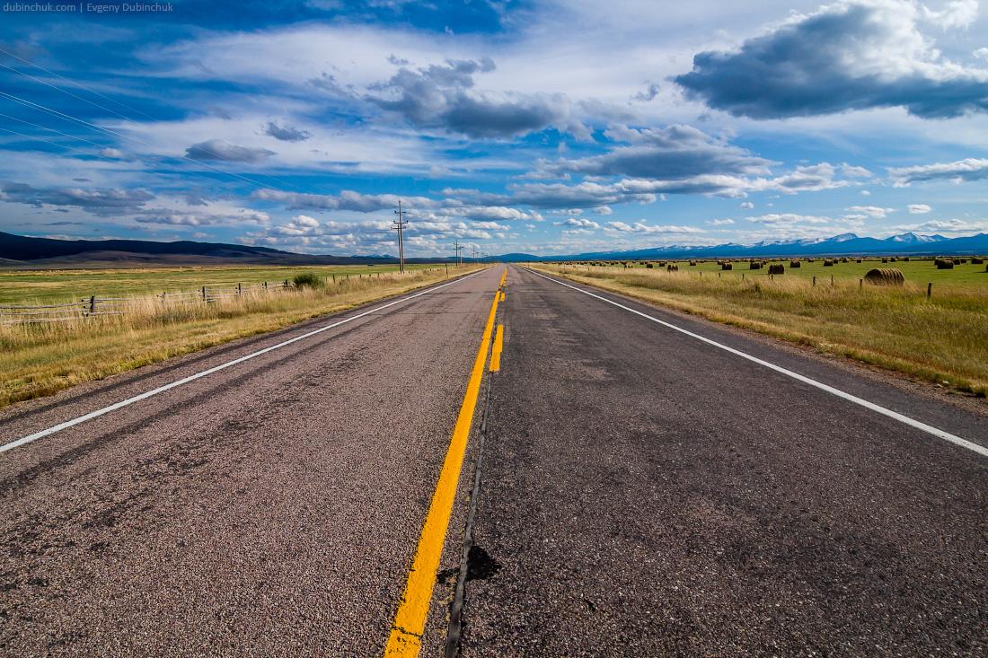 Пустая автострада в США. Путешествие на велосипеде в одиночке по Скалистым горам. Speed empty highway with blue sky and cirrus clouds