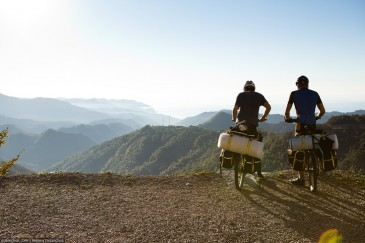 Two traveller cyclists looking from the top of the rock. Turkey