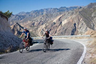 Two cyclists climbing to the pass on asphalt road in Turkey