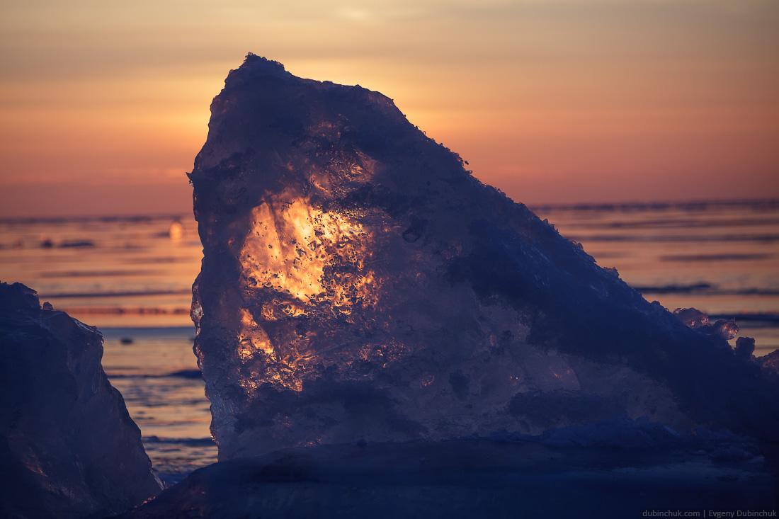 Льдина в торосах на Байкале на рассвете в лучах солнца. Путешествие на Байкал на коньках. Ice hummock on sunrise. Ice skating tour on Baikal lake.