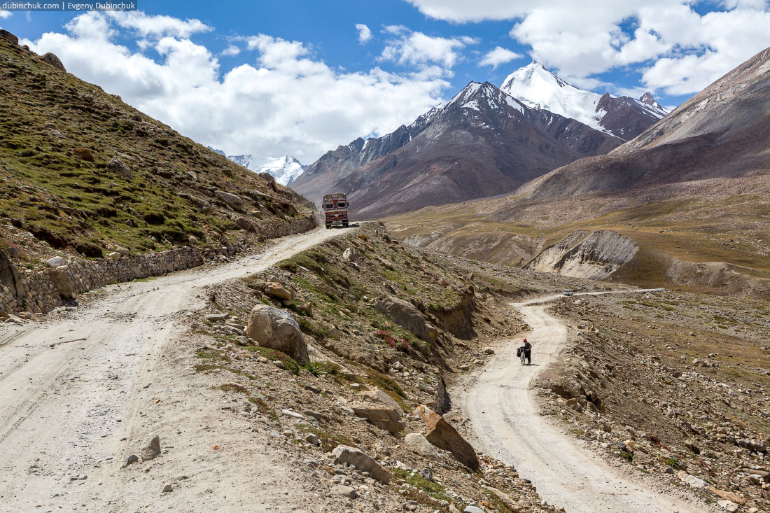 Велосипедистка и грузовик на повороте серпантина. Индия
