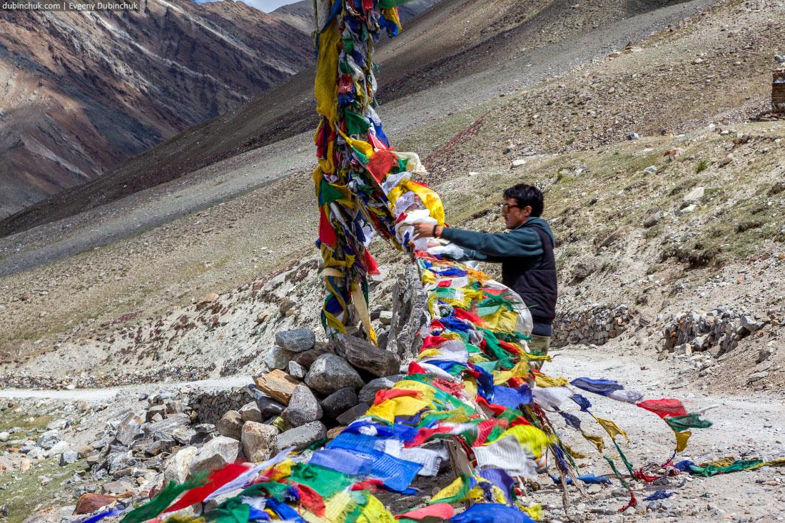 Индиец привязывает молитвенный флажок