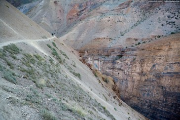 Steep slope and cyclist on narrow path in Zanskar Valley, Himalaya