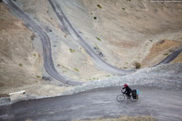 Cyclist on winding road. Himalayas, Ladakh, India