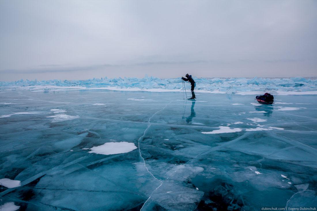 Путешествие на коньках по Байкалу зимой. Девушка на фоне синих торосов в пасмурную погоду