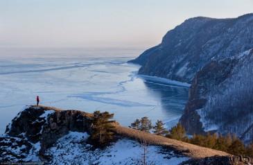 Путешественник на краю обрыва на озере Байкал зимой. Вид на замерзший лед с высоты птичьего полета
