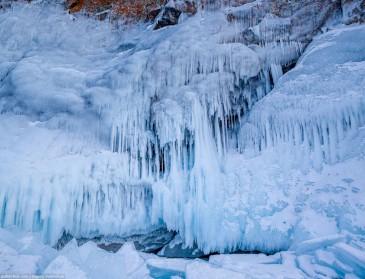 Обрывистый берег Байкала, покрытый сокуями - ледяными наплесками воды. Icy rocks on lake Baikal