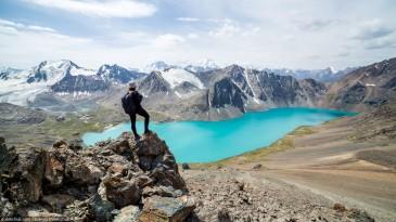 Hiker looking at Ala-Kul lake in Tien Shan mountains, Kyrgyzstan