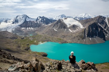 Traveller sitting and looking at Ala-Kul Lake. Tien Shan Mountains, Kyrgyzstan