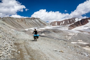 Cyclist in high Tien Shan Mountains near glacier