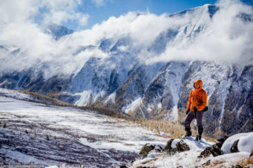 Hiker on the top of the pass in mountains of Altai