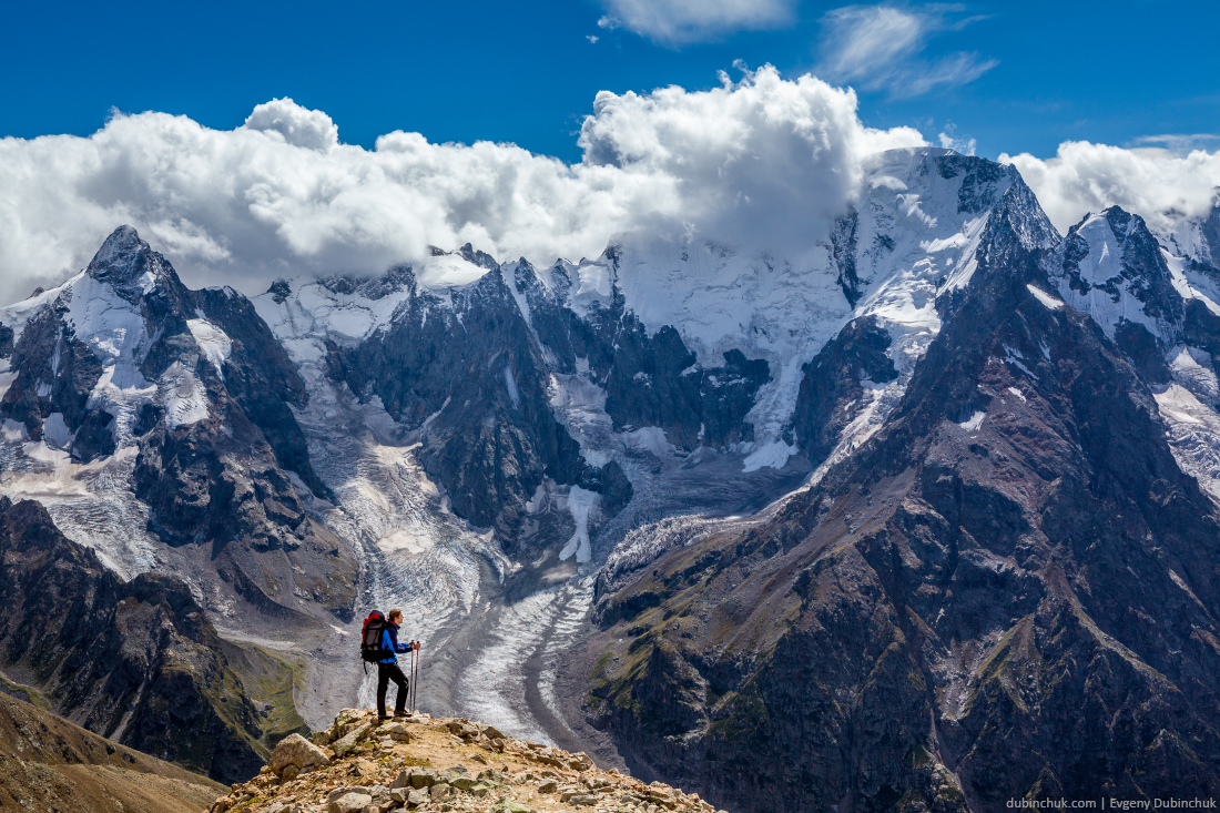 Hiker with backpack standing on mountain top and enjoying scene. Caucasus mountains, Russia