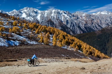 Adventure cyclist in Tibet mountains in autumn